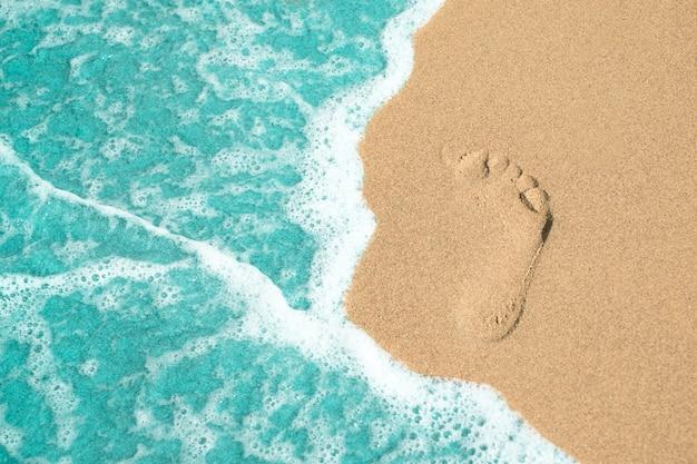 Sluit omhoog voetstap op zand bij het strand Gratis Foto