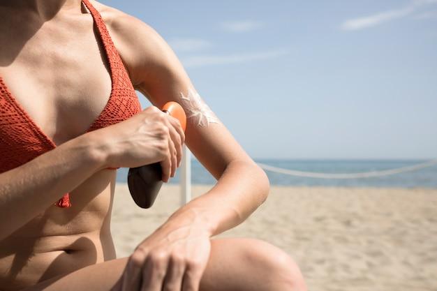 Sluit omhoog vrouw die zonnescherm op lichaam toepast Gratis Foto