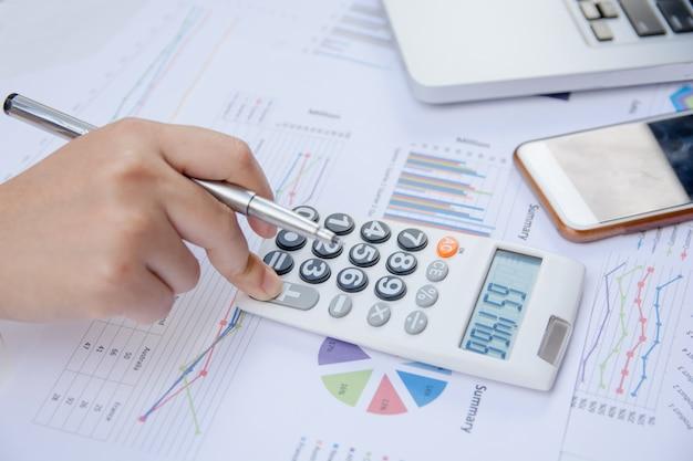 Sluit omhoog vrouw gebruikend calculator op document grafiekgegevens met het doen van financiën op kantoor. Premium Foto