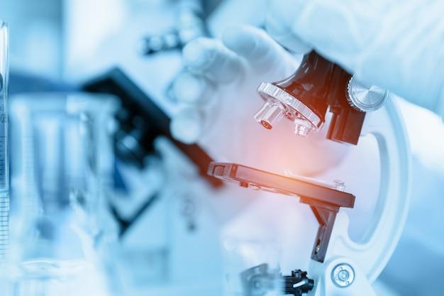 Sluit omhoog wetenschapper gebruikend microscoop in laboratoriumruimte terwijl het maken van medisch testen en onderzoek Premium Foto