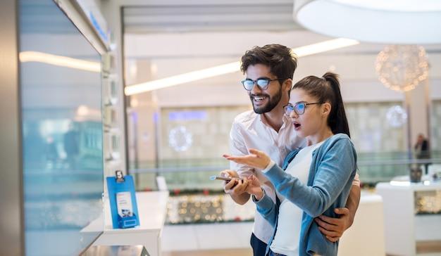 Sluit omhoog zijaanzicht van leuk opgewekt charmant jong studentenmeisje wijzend met handen op grote nieuwe tv terwijl haar gebaarde knappe glimlachende vriend die haar koestert in een technologie-opslag. Premium Foto