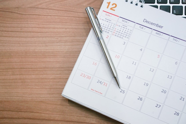 Sluit omhoog zilveren pen leg op kalender Premium Foto