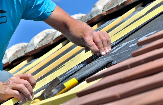 Sluit op de handen van een arbeider die e-dak van een huis vernieuwt Premium Foto