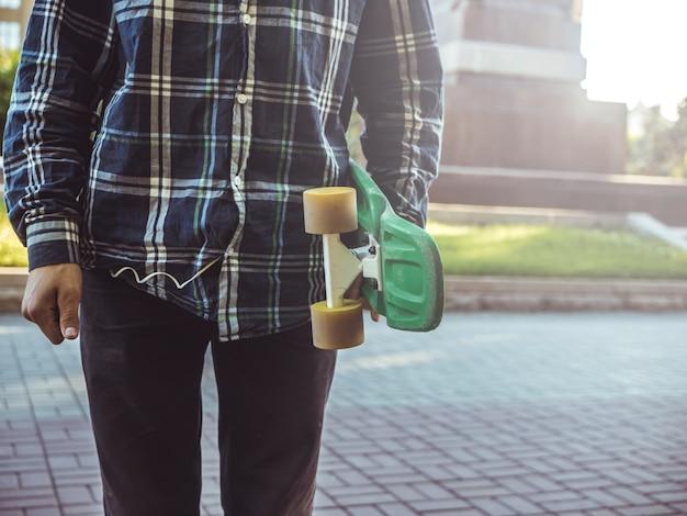 Sluit persoon in de de zomerstraat met stuiverskateboard op een zonnige dag Premium Foto