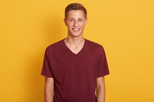 Sluit portret van tevreden jonge kerel kleedde kastanjebruine toevallige t-shirt, bekijkend glimlachend camera, drukt happyness, het model stellen geïsoleerd op geel uit. mensen, jeugd en lifestyle concept. Gratis Foto
