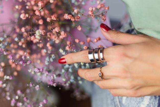 Sluit schot van de vingers van de vrouwenhand die twee ringen, boeket van kleurrijke droge bloemen dragen Gratis Foto