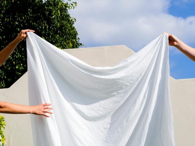 Sluit twee mensen omhoog hangend een wit blad op de lijn Gratis Foto