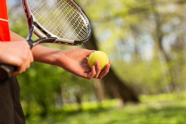 Sluit van de handen van mensen houden omhoog een tennisracket en een bal op de groene achtergrond. Premium Foto