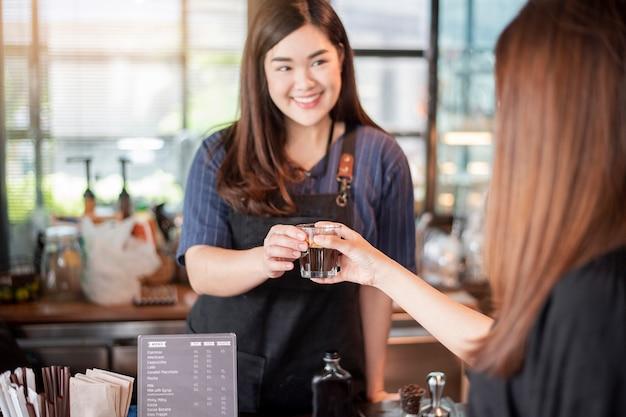 Sluit van vrouwelijke hand neemt omhoog hete koffie van barista Premium Foto