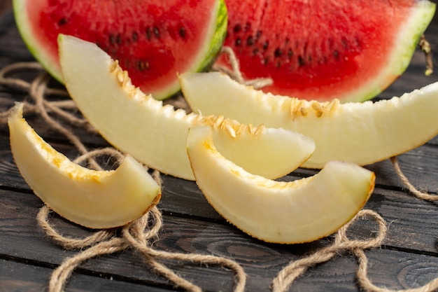 Sluit vooraanzicht gesneden verse watermeloen half gesneden zoet fruit met meloen op de bruine rustieke achtergrond Gratis Foto