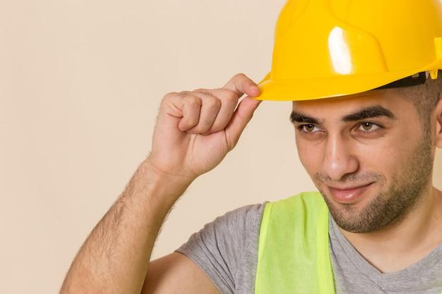 Sluit vooraanzicht mannelijke bouwer in gele helm poseren op lichte achtergrond Gratis Foto