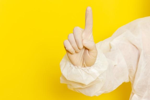 Sluit vooraanzicht van mannelijke wetenschappelijke werker in speciaal beschermend pak dat zijn vinger op gele muur opheft Gratis Foto