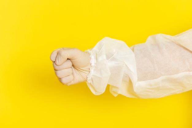 Sluit vooraanzicht van mannelijke wetenschappelijke werker in speciaal beschermend pak op gele muur Gratis Foto