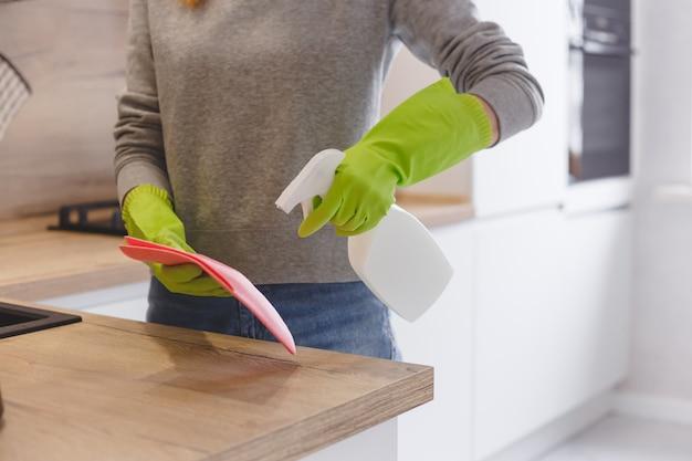 Sluit vrouwen omhoog schoonmakende keuken gebruikend reinigingsmiddelnevel en doek. Premium Foto