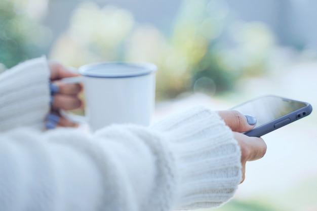 Sluit vrouwenhanden omhoog houdend hete kop van koffie of thee en gebruikend smartphone op koude weerachtergrond, dragend warme bont gebreide kleren Premium Foto