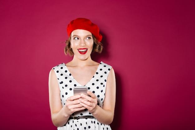 Sluwe glimlachende gembervrouw in smartphone van de kledingsholding en het kijken weg over roze Gratis Foto