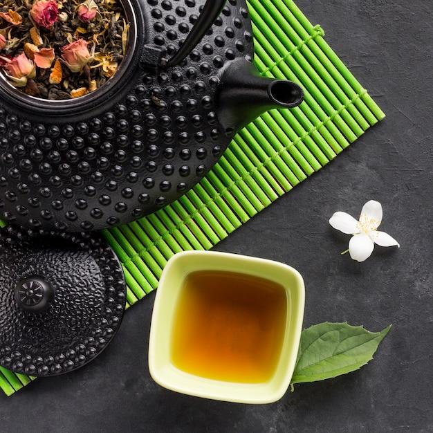 Smakelijk aftreksel en droog theekruid met witte jasmijnbloem op zwarte achtergrond Gratis Foto