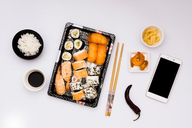 Smakelijk aziatisch voedsel met mobiele telefoon dat over witte oppervlakte wordt geïsoleerd Gratis Foto