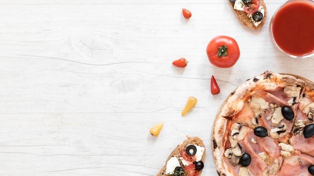 Smakelijke bacon en paddestoelpizza dichtbij tomatensaus en broodsandwich over wit bureau met ruimte voor tekst Gratis Foto