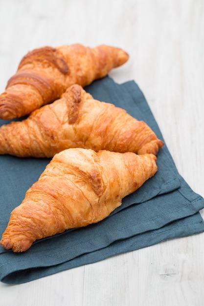 Smakelijke boterachtige croissants op oude houten tafel. Premium Foto