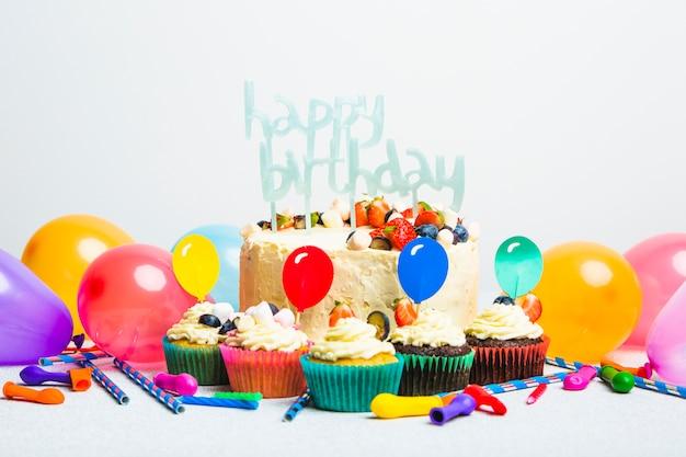 Smakelijke cake met bessen en gelukkige verjaardagstitel dichtbij reeks muffins en ballons Gratis Foto