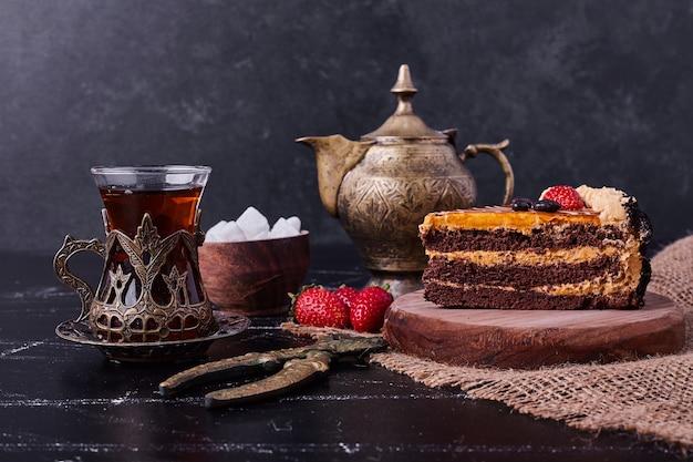 Smakelijke chocoladetaart met theeset op donkere achtergrond. Gratis Foto