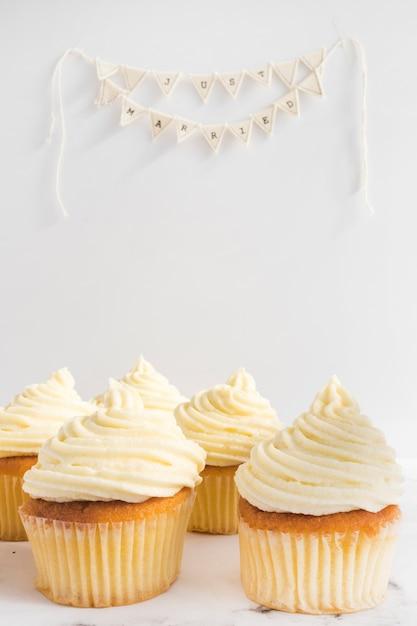 Smakelijke cupcakes en net getrouwd gors op witte achtergrond Gratis Foto