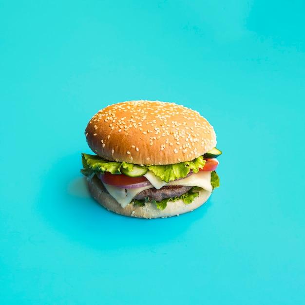 Smakelijke hamburger op blauwe achtergrond Gratis Foto