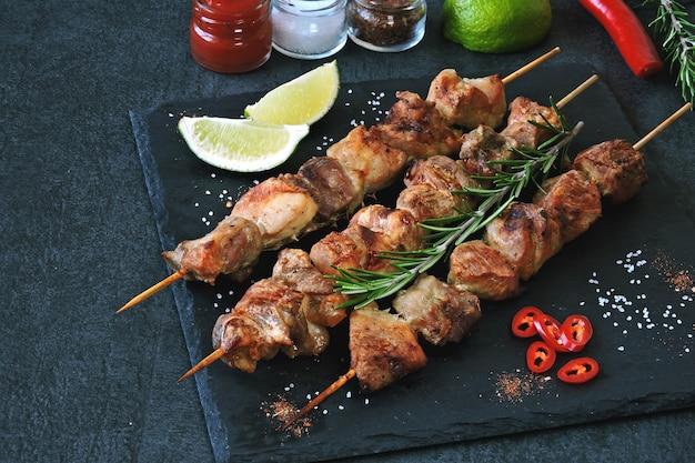 Smakelijke kebab met kruiden, chili en limoen. geurige spiesjes van varkensvlees op een stenen bord. Premium Foto