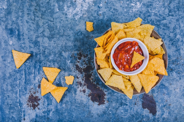 Smakelijke mexicaanse nachos met salsa saus op verweerde achtergrond Gratis Foto