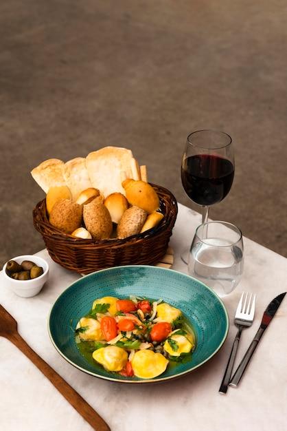 Smakelijke pasta en mandje brood met wijn op tafel Gratis Foto
