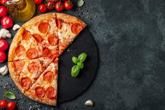 Smakelijke pepperonispizza op een zwarte concrete achtergrond. Premium Foto