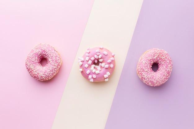 Smakelijke roze geglazuurde donuts bovenaanzicht Gratis Foto