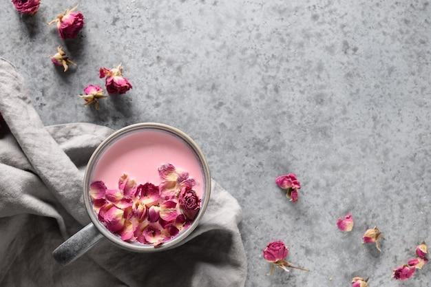 Smakelijke rozenmaanmelk in grijze kop en rozenblaadjes op grijze achtergrond. uitzicht van boven. ruimte voor tekst. Premium Foto