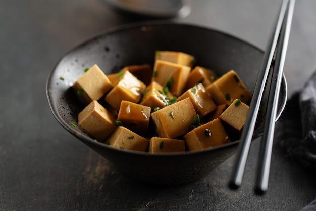 Smakelijke smakelijke stukjes tofu met saus geserveerd in kom klaar om te eten. detailopname. Gratis Foto