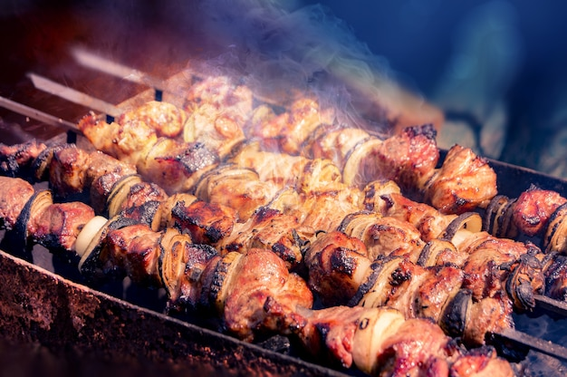 Smakelijke stukjes gemarineerd vlees, uien en groenten worden aan spiesjes geregen en worden op houtskoolgrills gekookt in aromatische hete rook. detailopname Premium Foto