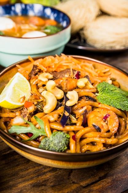 Smakelijke thaise udonnoedels met rundvlees; broccoli; munt; noten en citroen in kom op houten tafel Gratis Foto