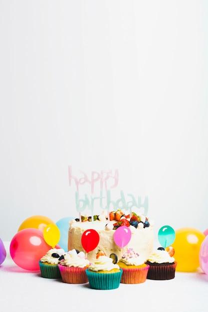 Smakelijke verse cake met bessen en gelukkige verjaardagstitel dichtbij reeks muffins en ballons Gratis Foto