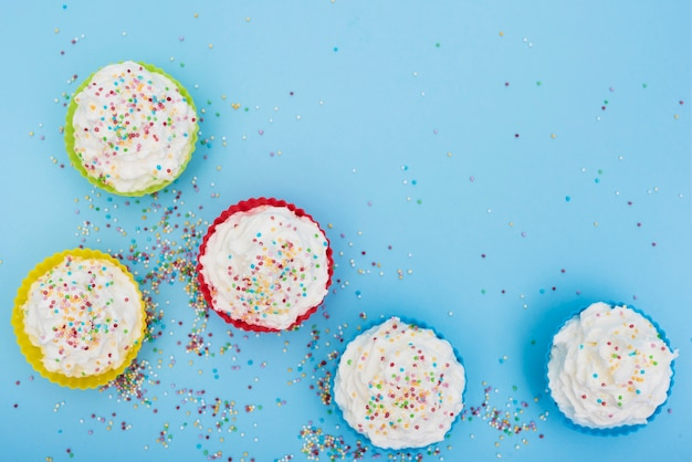 Smakelijke versierde cakes op blauwe achtergrond Gratis Foto