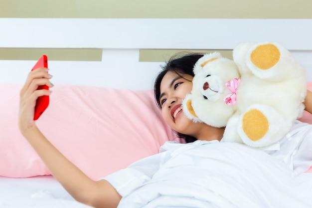 Smartphone die van het tiener vrouwelijke gebruik op het bed babbelt Gratis Foto
