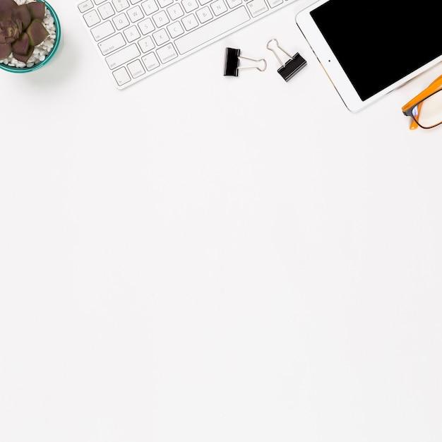 Smartphone en kantoorbenodigdheden op witte achtergrond Gratis Foto