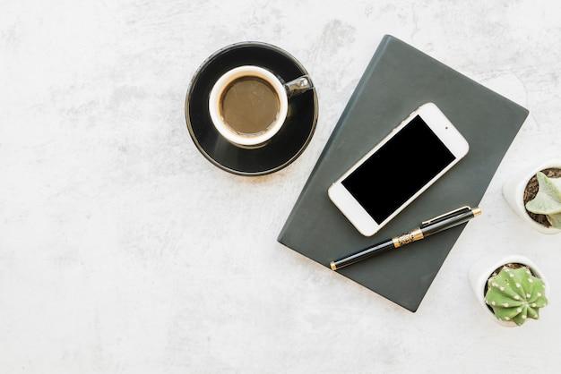 Smartphone en koffie op tafel met laptop Gratis Foto
