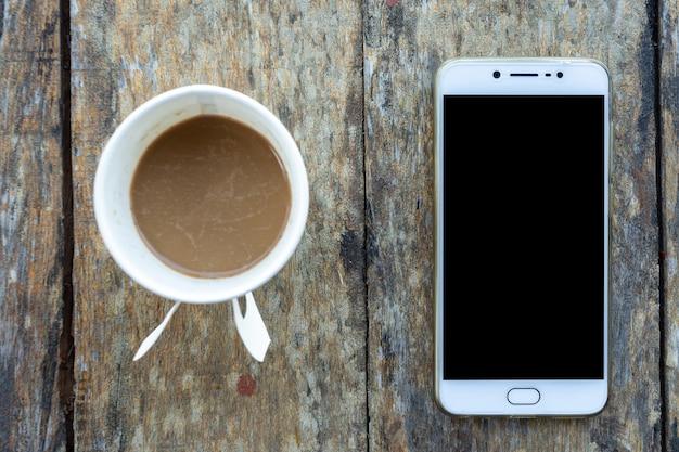 Smartphone en koffiekopje gemaakt van papier op oud houten bureau op bovenaanzicht. Premium Foto