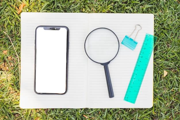 Smartphone en vergrootglas op de top van geopende notebook Gratis Foto