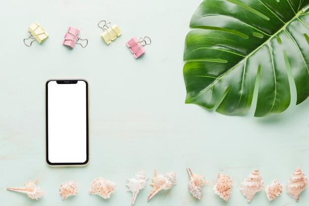 Smartphone met decoratieve elementen op lichte achtergrond Gratis Foto