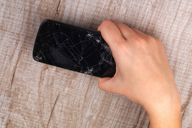 Smartphone met een gebroken scherm in de hand van het meisje Premium Foto