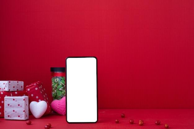 Smartphone met een leeg scherm en geschenkdozen en harten. valentine samenstelling Premium Foto