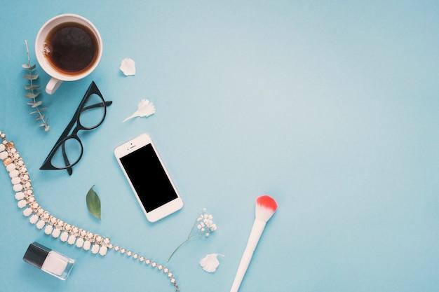 Smartphone met glazen, theekop en bloemen Gratis Foto
