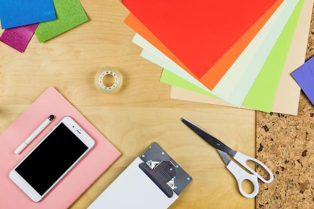 Smartphone met helder papier op tafel Gratis Foto