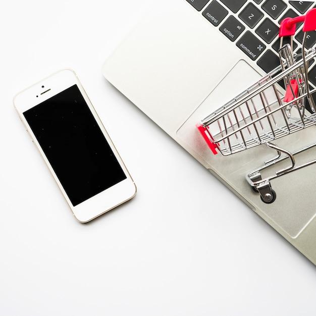 Smartphone met kleine boodschappenwagentje Gratis Foto